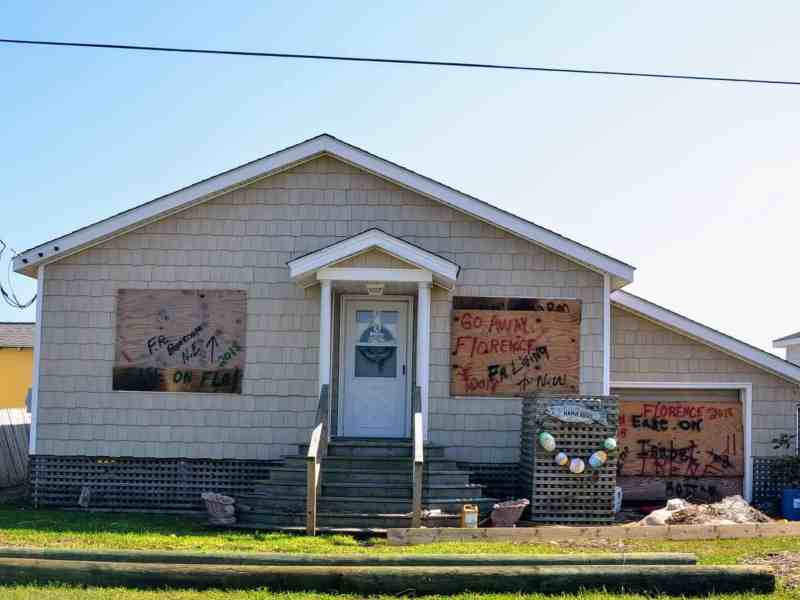 """Shows a boarded up cottage with plywood over the windows. On the plywood is spraypainted: """"Go Away FLorence"""""""