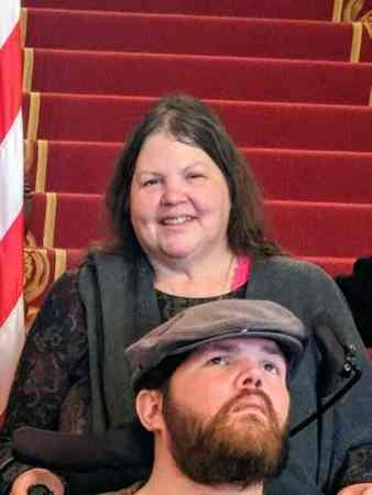 A woman stands behind her son who is in a wheelchair with red carpeted stairs behind them