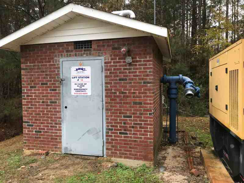 """Photo shows a simple brick pump house with a sign on the door that reads, """"In case of alarm or emergency call..."""""""