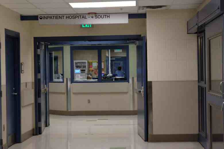 """shows open doors leading into a corridor with heavy windows. An overhead sign reads """"Inpatient hospital, 4 South"""""""