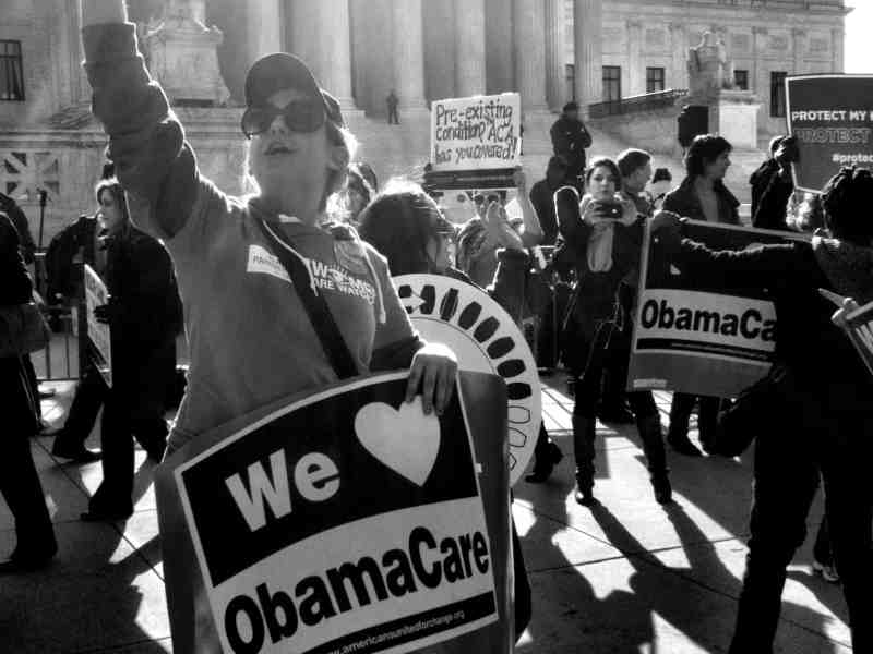 """black and white photo shows a woman standing in front of a large greek temple styled building, holding a sign that reads """"We HEART Obamacare"""""""