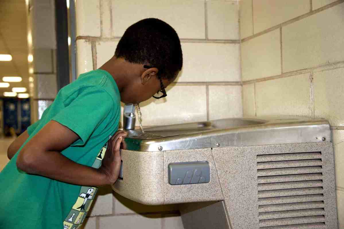 a little boy drinks at a water fountain that appears to be in the hallway of a school. Children are particularly vulnerable to lead exposure, and they can get it through drinking contaminated water.