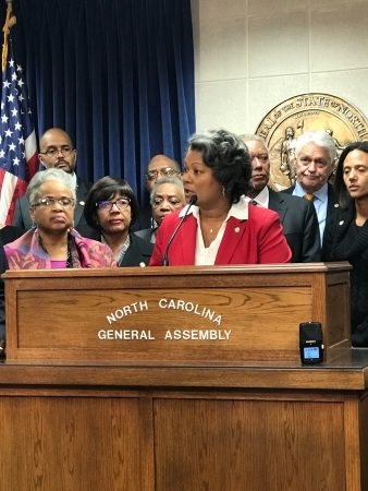 shows Cunningham speaking at a podium that reads: North Carolina General Assembly. She surrounded by other people.