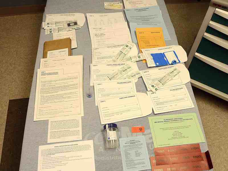 shows documents and medical instruments spread out on display on a gurney