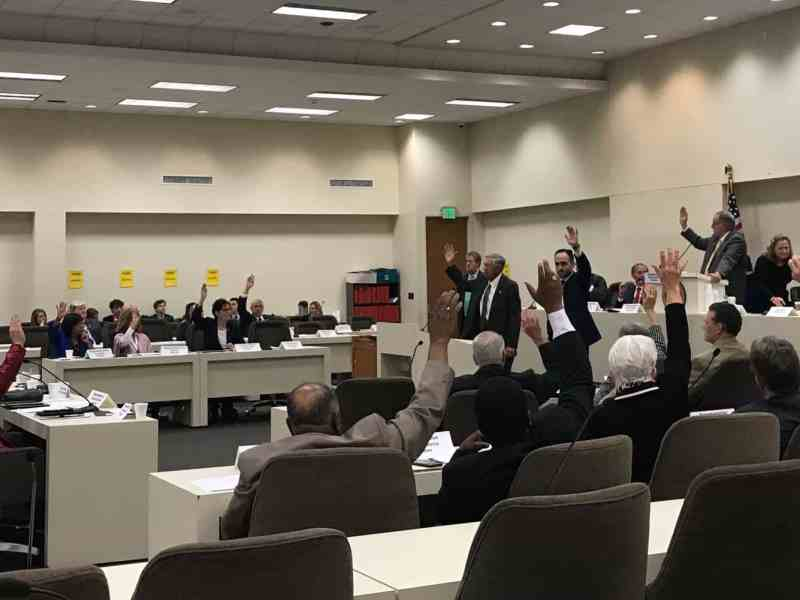 shows a legislative committee room, most of the lawmakers have their hands in the air