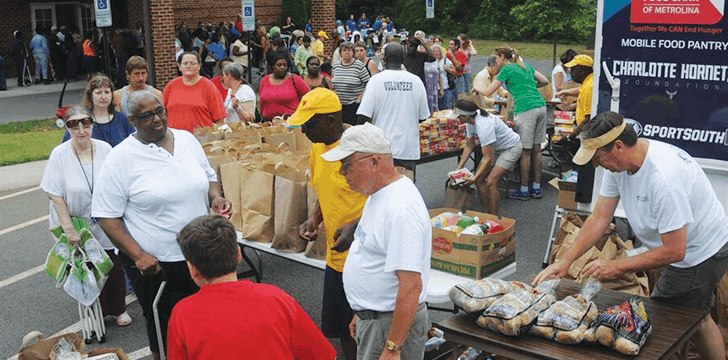 shows people crowded around the back of a truck whr there's food displayed on tables.