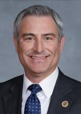 shows a smiling man in a suit and tie