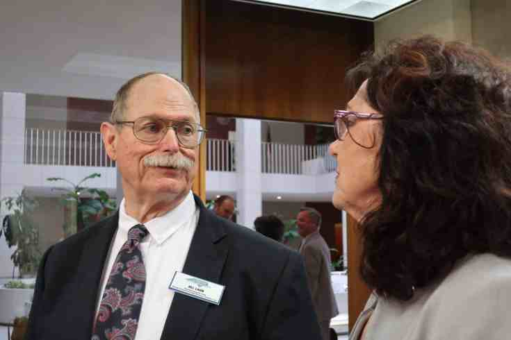 older man with a mustache speaks to a woman who's partially turned away from the camera