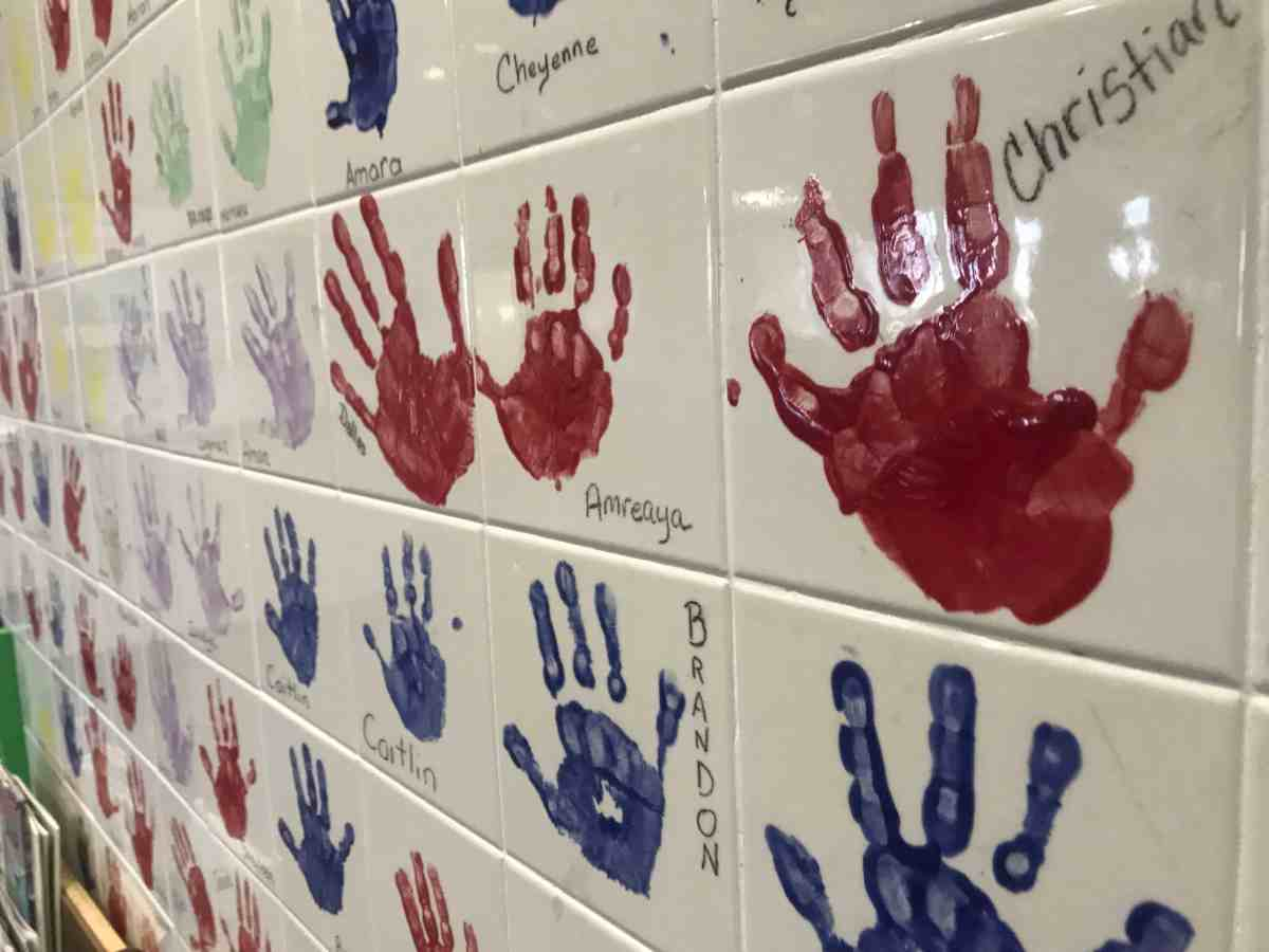 shows a tile wall, each tile has the handprint of a child and some text on it as a proxy for child abuse