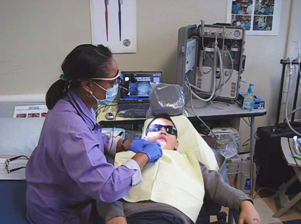 shows a woman caring for a patient who is in the dental chair. She has a gown, goggles and gloves on, and is looking at a teledentistry camera that's in the office.