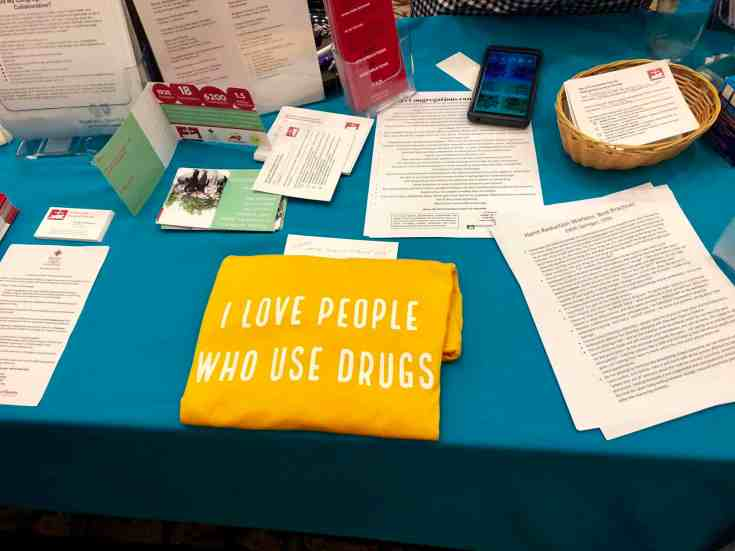 """A display of informational materials, including pamphlets, printed papers, cards and a t shirt reading """"I love people who use drugs"""""""