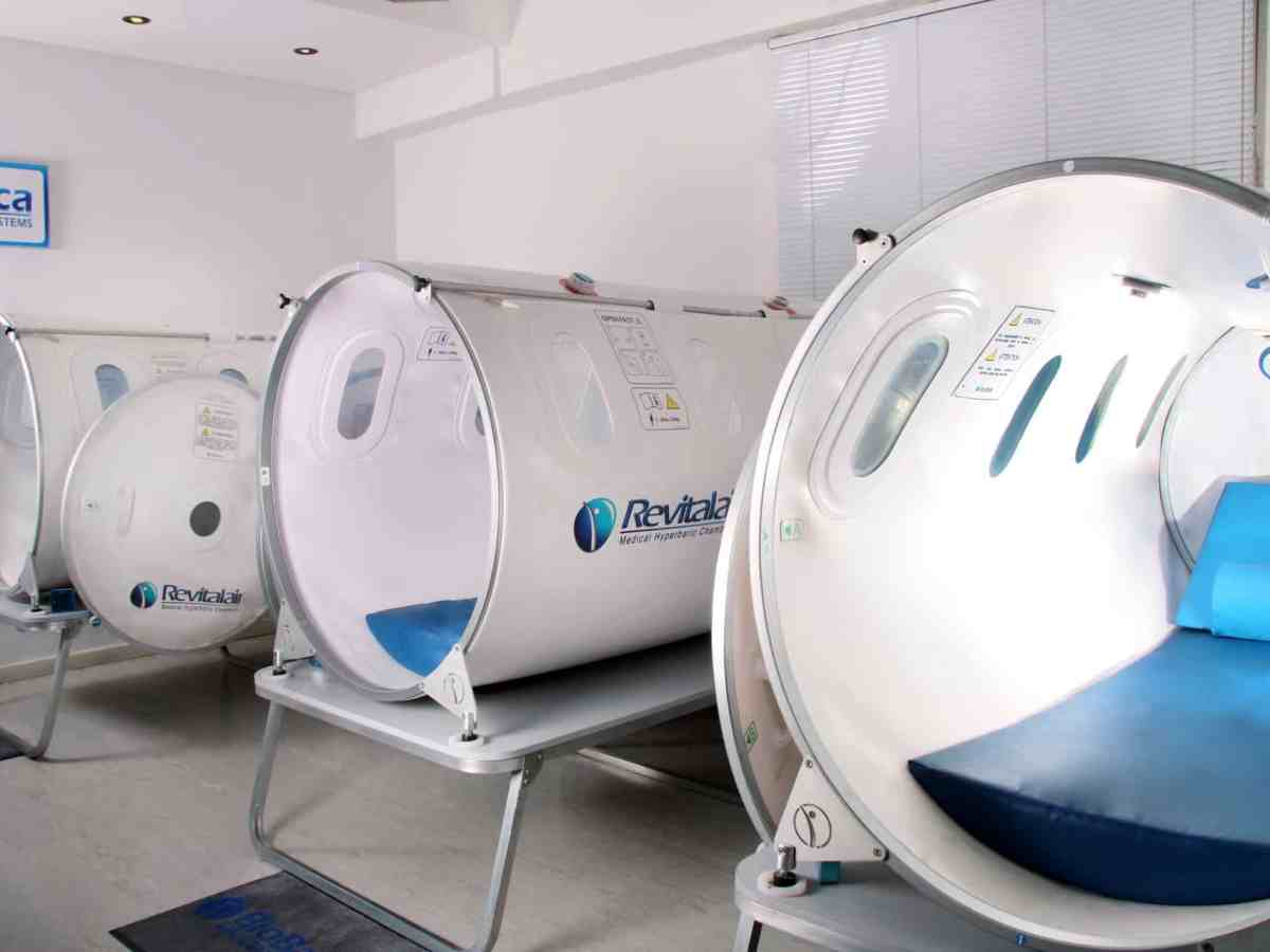 shows three empty hyperbaric oxygen treatment chambers, they look like large tubes that you can lay down in.
