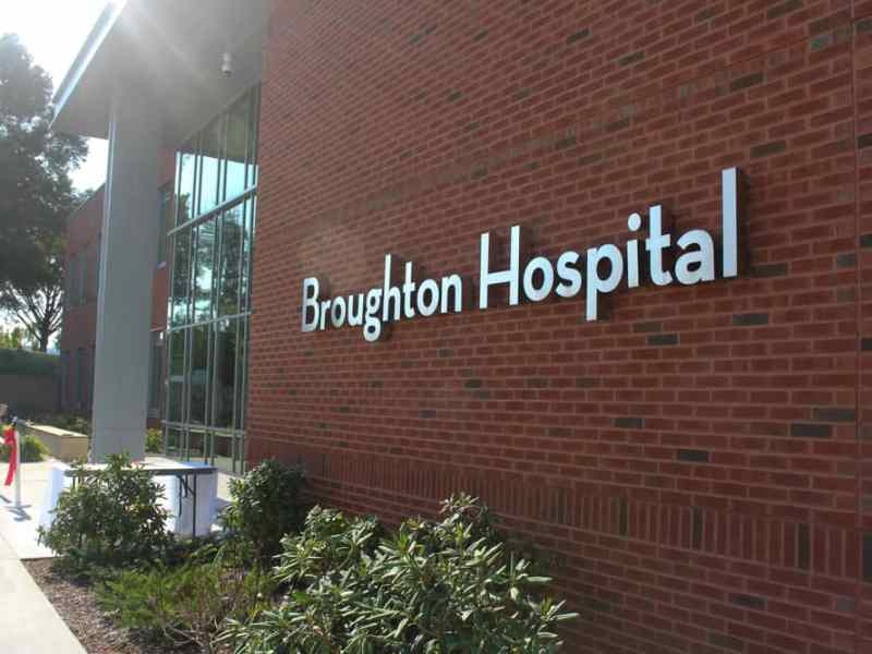 """A red brick building with metal lettering that says """"Broughton Hospital."""" In front of the building is a red ribbon for the ribbon cutting ceremony."""