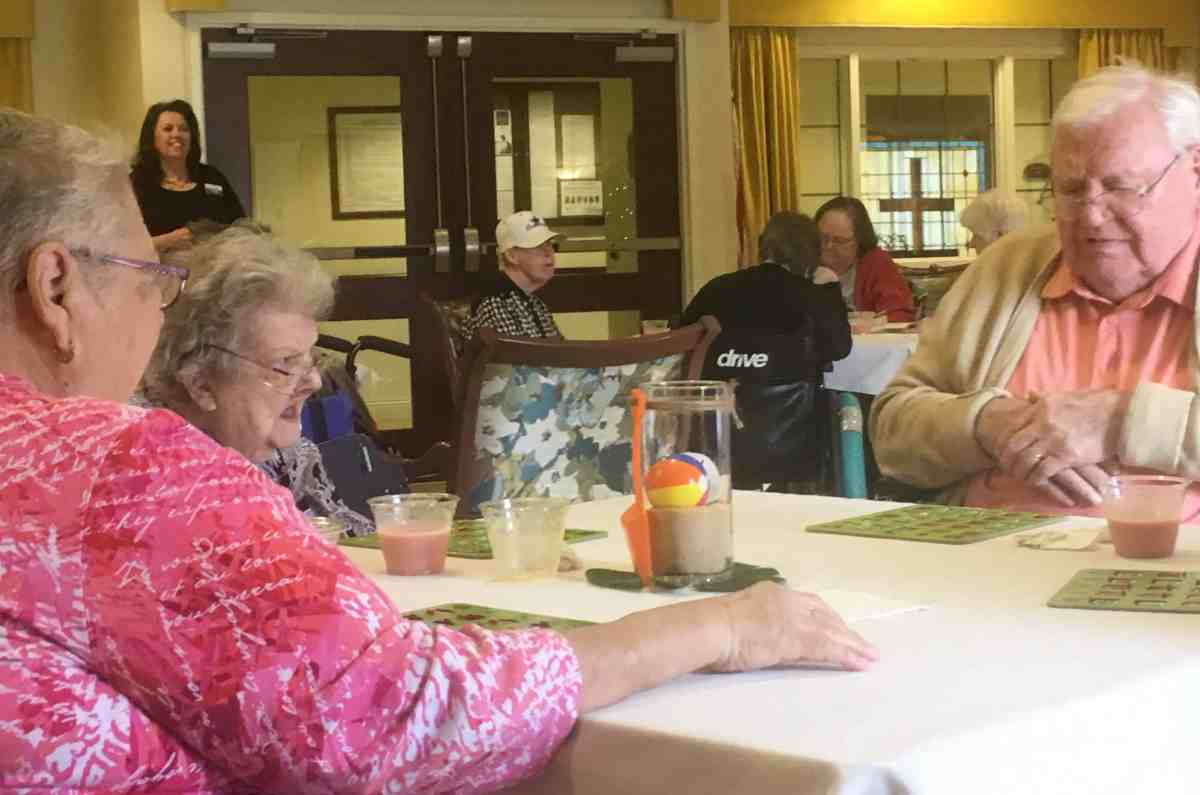 shows three elderly people playing bingo.