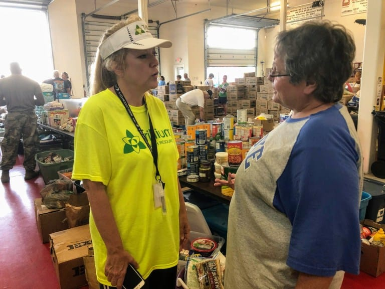"""a woman in a bright yellow t shirt that reads """"Trillium"""" speaks with another woman in a room crowded with people and supplies piled on the floor."""