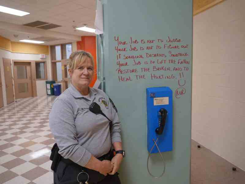 A woman in a gray polo looks at the camera leaning against a light green column which holds a pay phone and a handwritten note