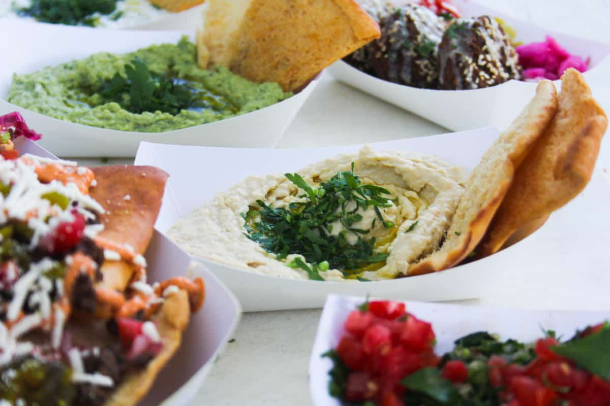 Paper boats with different types of Middle Eastern Foods are lined up. This is an example of healthy food at the North Carolina State Fair