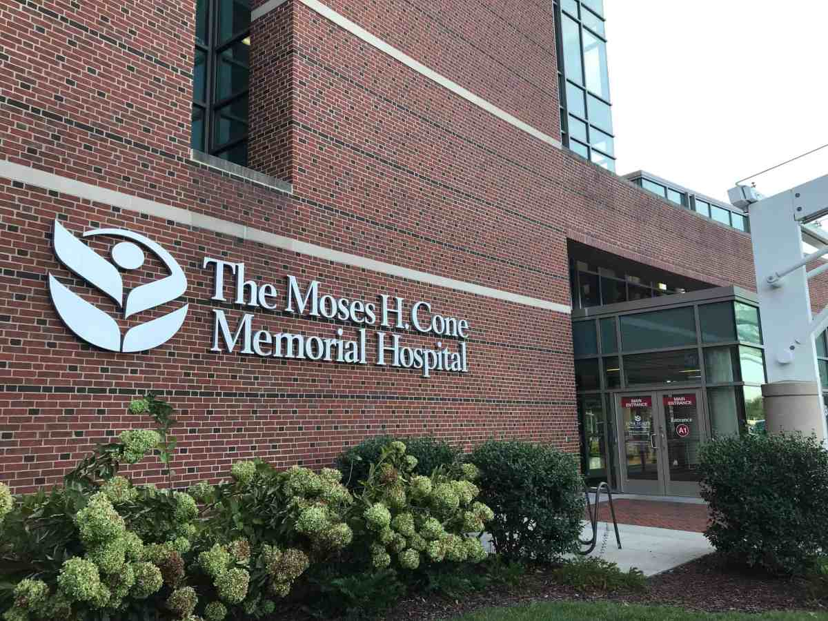 """The entrance to a red brick building with a sign that says """"The Moses H. Cone Memorial Hospital"""""""