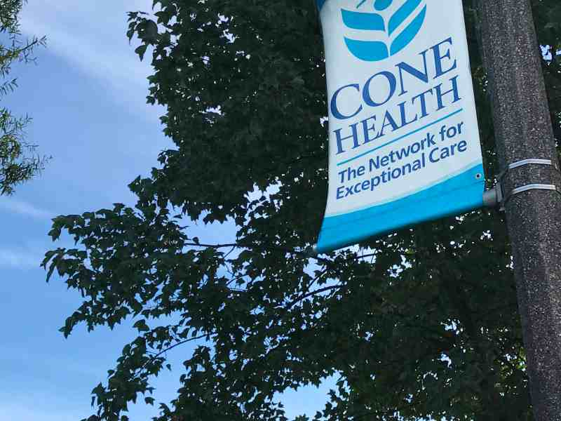 A photo of a Cone Health sign with a tree and sky background