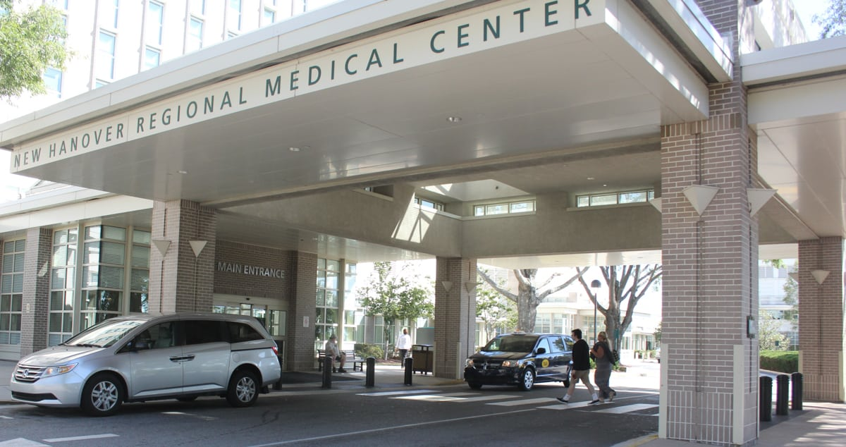 """A hospital main entrance is visible, with the words """" New Hanover Regional Medical Center."""" The entrance is made of brick and there are cars and people under the brick canopy that leads to the main part of the hospital."""