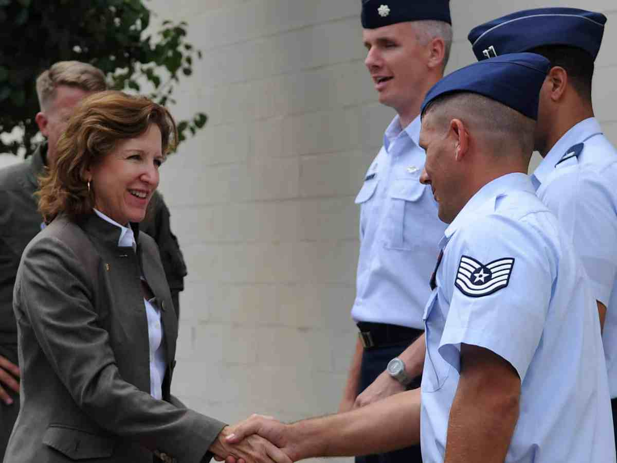 A woman in a suit shakes hands with a man in uniform. She's former Senator Kay Hagan, who recently died of a rare tick-borne virus.