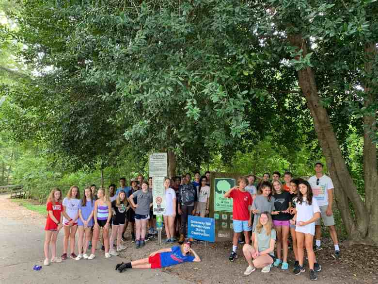 Students pose for a photo in a park. Students from Exploris are studying PFAS for a class project.