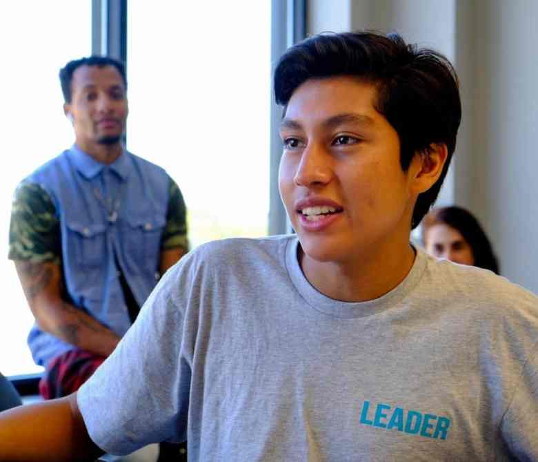 Smiling teen in a gray t-shirt with the word leader