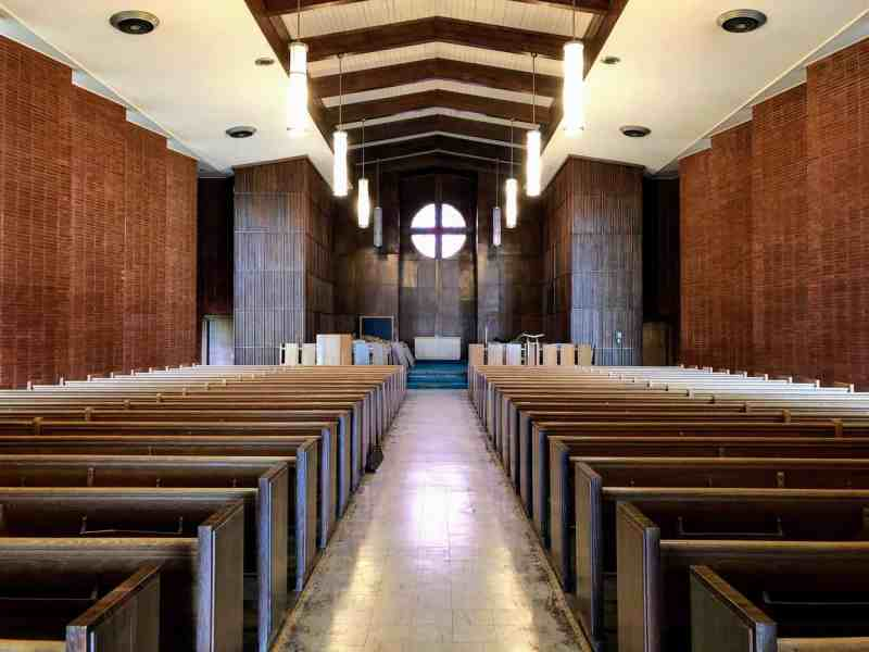 A look inside the former Dorothea Dix Chapel, which features dark wooden pews and ornate panels.