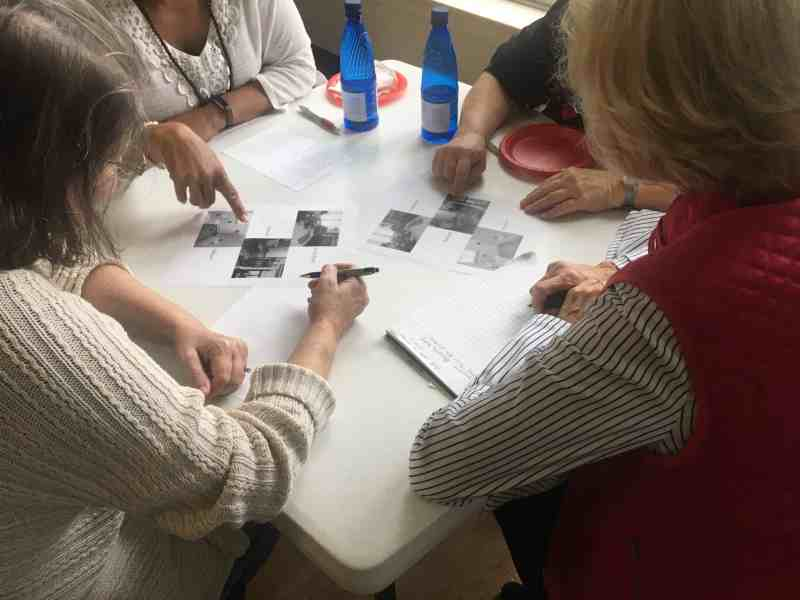 Participants in a falls prevention workshop look at photos of common household hazards around a white table.
