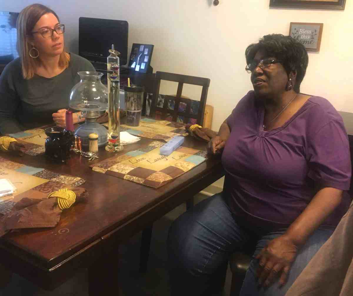 Two women sit near a table and talk. One of them is a volunteer caregiver
