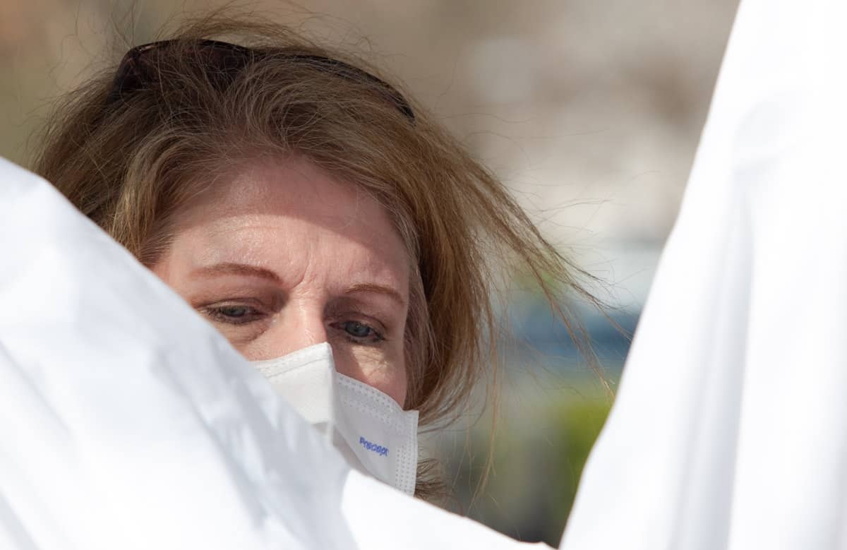 we see the top of a woman's face. She has on a mask agains the novel coronavirus