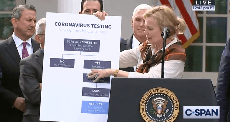 a woman stands at a podium, talking about coronavirus