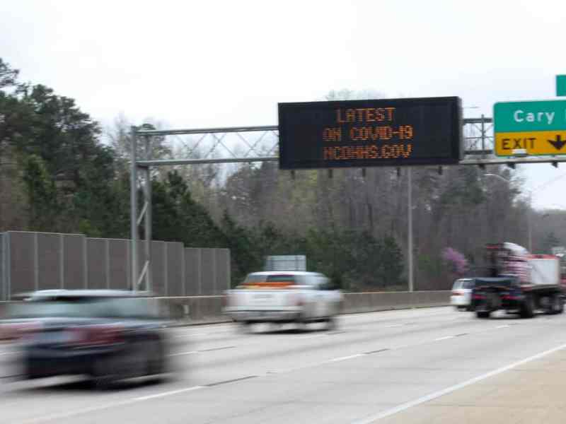 A sign that says latest on COVID-19 NCDHHS.Gov near Exist 99 on Route 1