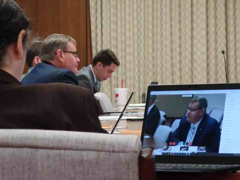 shows a man and in the foreground, on a laptop the same man appears on a videoconference about coronavirus