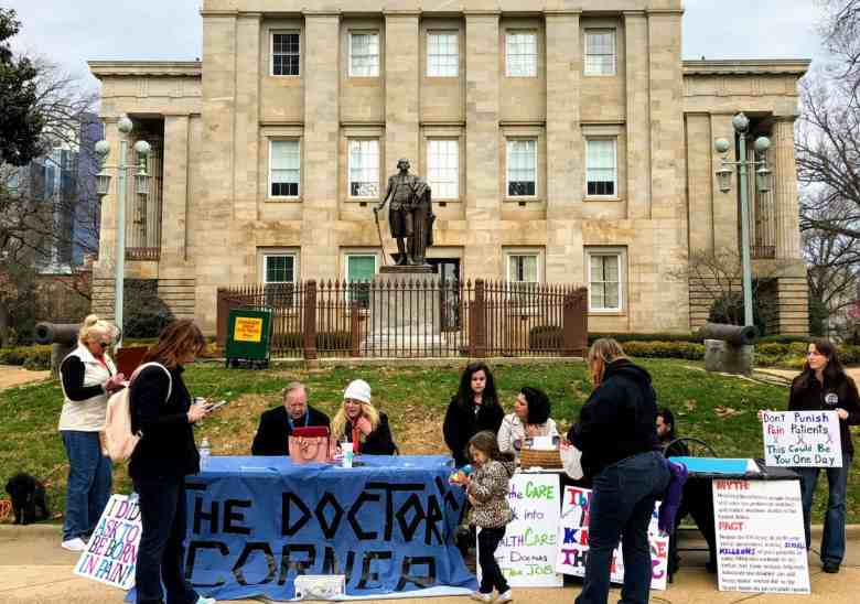 a group of people with posters stands in front of the old capital building in Raleigh. This is a rally to support Thomas Kline, a docotor who treats chronic pain patients.