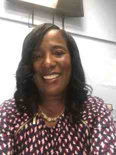 A child care center owner is an African-American woman with long black hair.