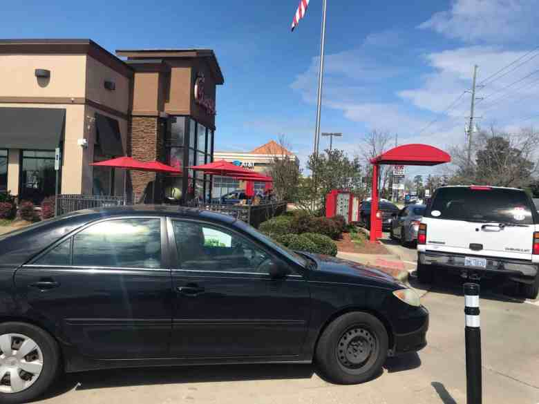 Cars line up at a Chick-Fil-A drive-thru in Fayetteville. The restaurant is among the first to close inside dining as a precaution because of the coronavirus