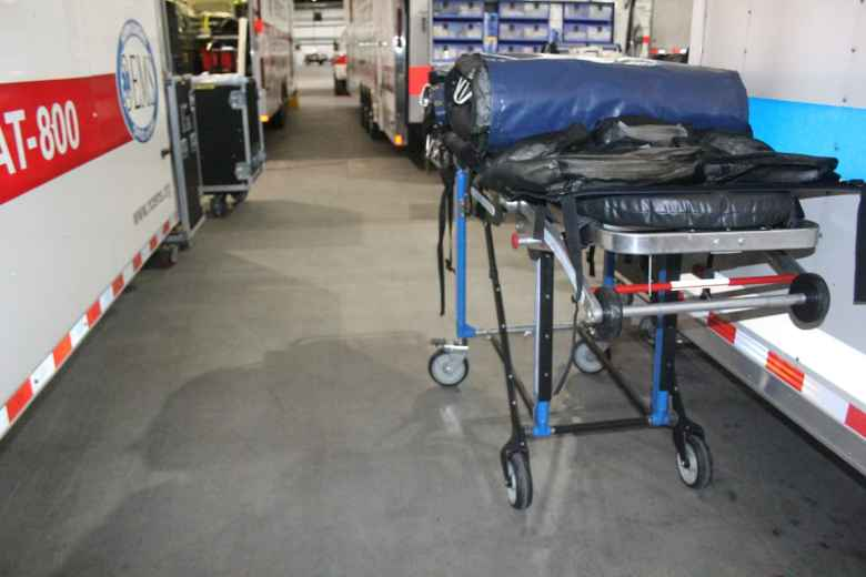 A gurney with supplies on it is visible in a warehouse. The gurney is part of WakeMed's emergency preparedness supplies.