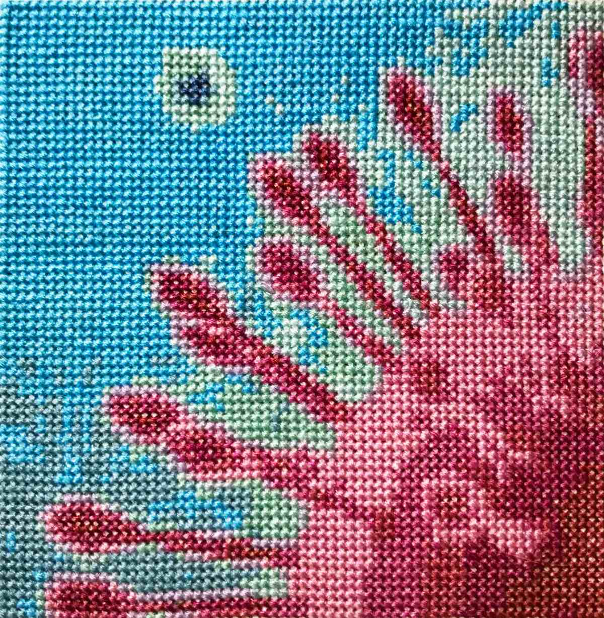 A cross stitched pattern of the novel coronavirus, COVID-19,a round shape with spikes coming out of it.