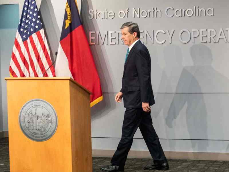 Gov. Cooper walks to a podium with flags in the background. He's at a coronavirus (COVID-19) briefing.