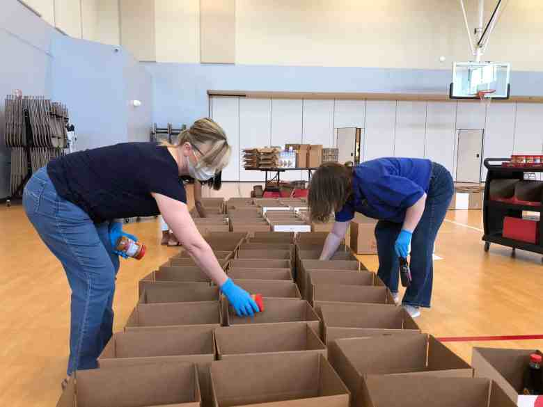 shows several women putting food such as peanut butter into rows of cardboard boxes