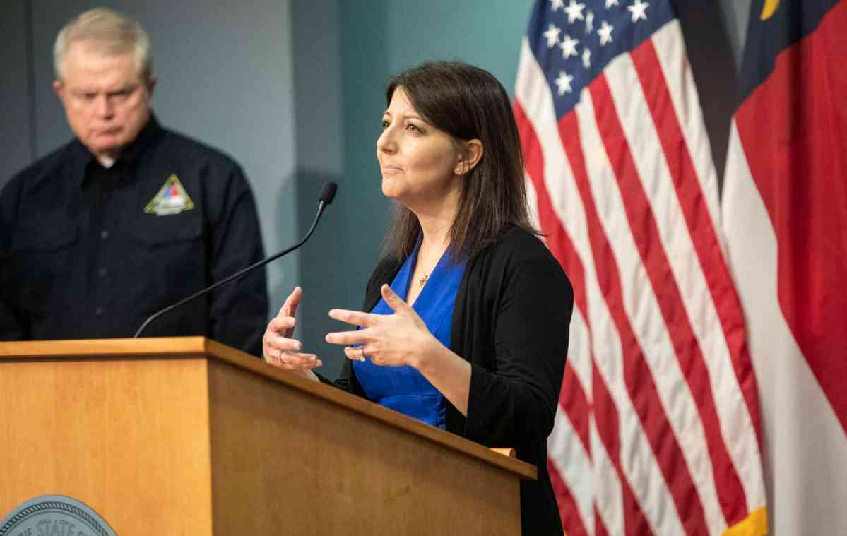 Sec. Mandy Cohen stands at a podium. Mike Sprayberry is in the background and he's blurry. They're talking at a coronavirus briefing.
