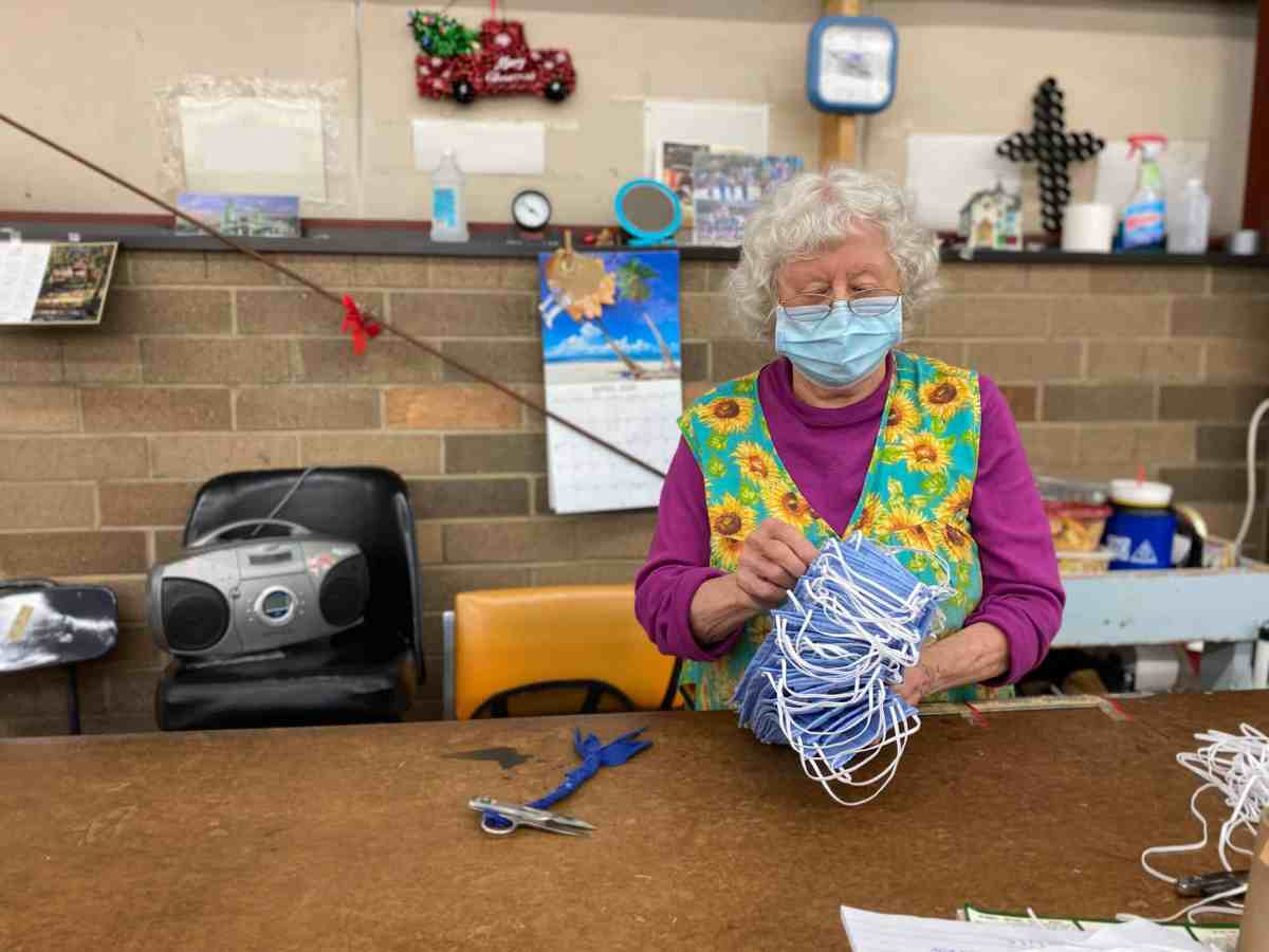 A woman looks at cloth masks in her hands. The masks were created to help combat the coronavirus pandemic