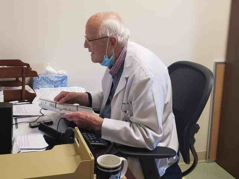 A physician in a white coat is sitting in front of a computer to do a virtual appointment via telehealth