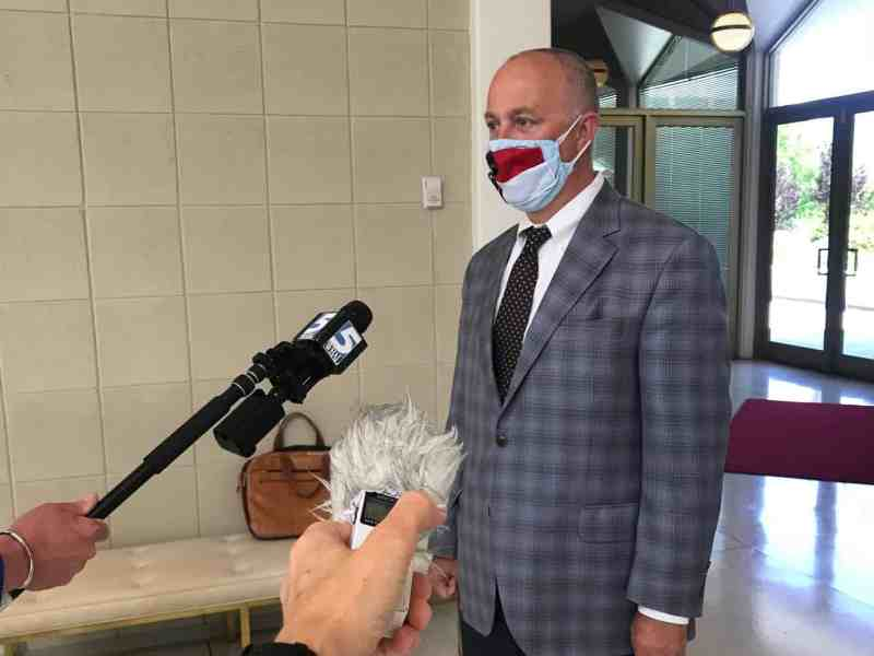 man in a suit and a mask with the North Carolina flag sewn onto the front, worn as a protection against coronavirus