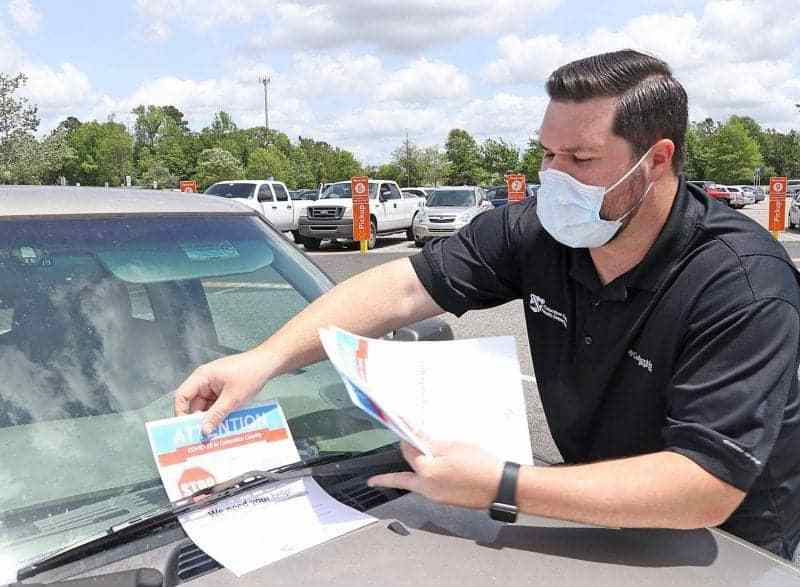A man in a facemask puts a coronavirus awarness flier on a car at a wal-Mart parking lot in Columbus County, a rural area.