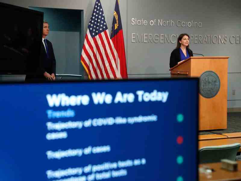 shows a computer screen in the foreground with statistics about COVID on the screen, a woman stands at a podium in t he distance.