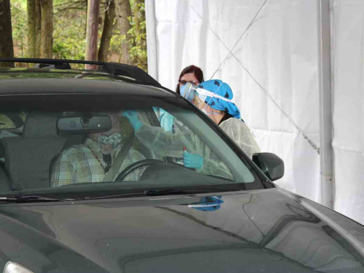 shows health care workers in full protective gear testing someone sitting in their car for COVID