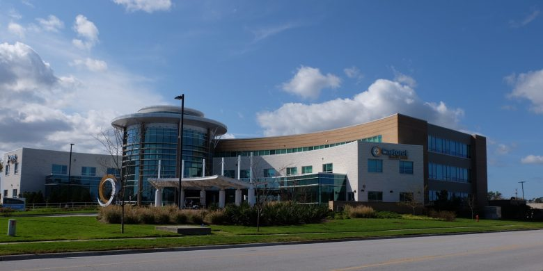 shows a hospital building with big fluffy clouds behind