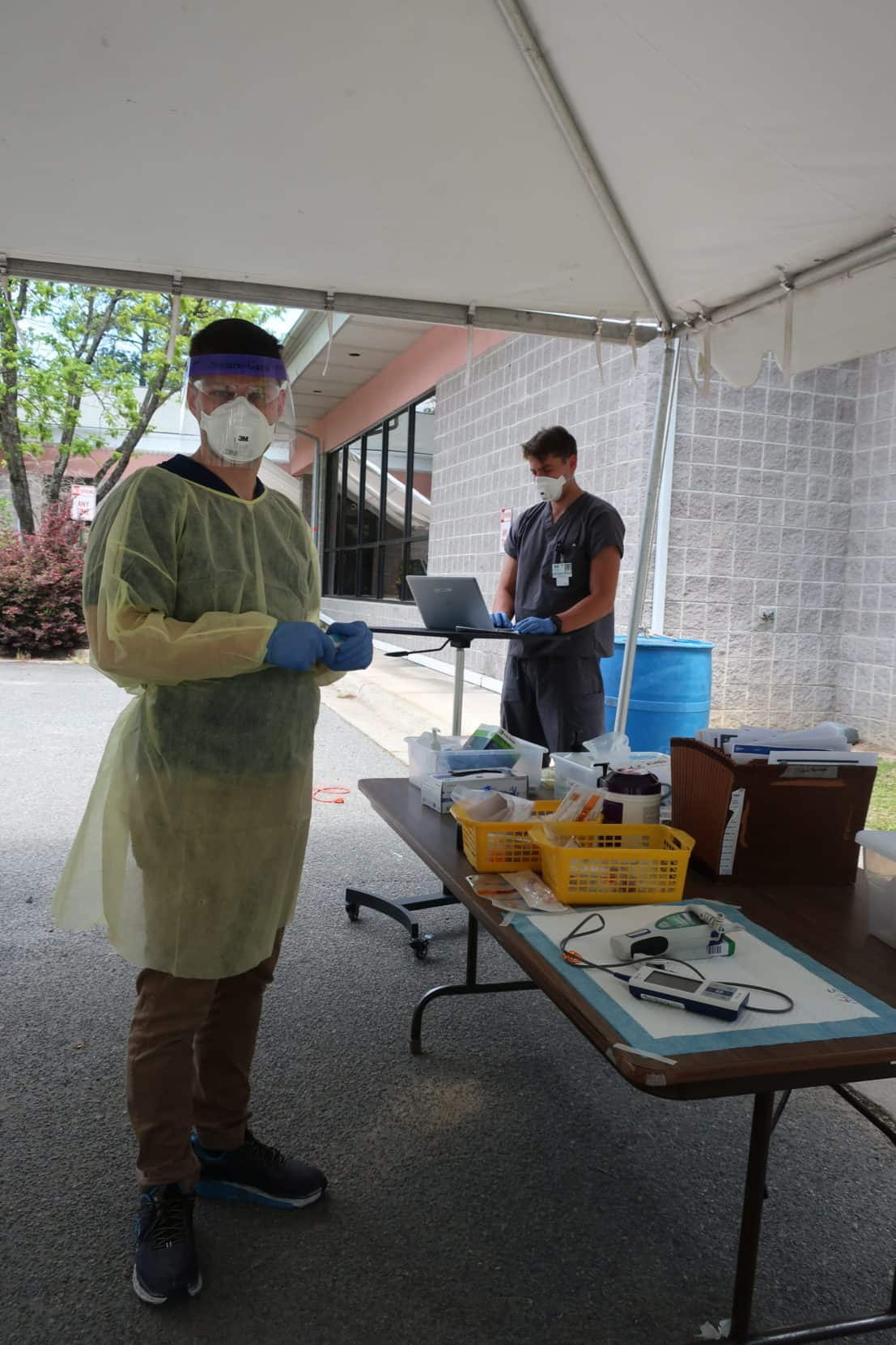 shows a man in personal protective equipment standing with testing equipment in his hands. He's standing under a tent, where they're doing drive through testing and vaccines for COVID-19